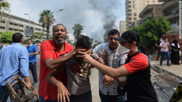 Supporters of Morsy and members of the Muslim Brotherhood run from tear gas as security forces move in at the site of a pro-Morsy sit-in in Cairo on August 14.