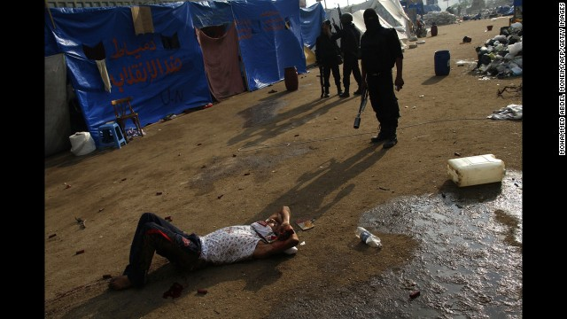 Riot police stand behind a wounded man near Rabaa al-Adawiya mosque in Cairo on August 14.