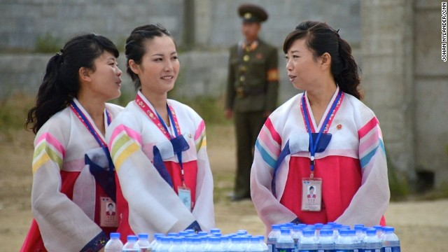Guides from the local tourist bureau handing out water bottles to bikers, monitored by a guard in the background.