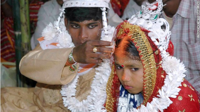 An Indian groom puts the holy mark on the forehead of his underage bride during a mass marriage program in 2006.