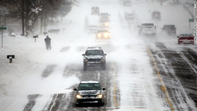 Vehicles drive down a snow-covered road in Burton, Michigan, on January 6.