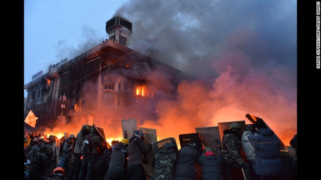 Protesters protect themselves with shields as they clash with police in Kiev on February 19.
