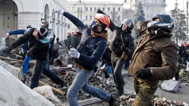 Protesters in Kiev throw rocks at riot police in Independence Square on February 19.