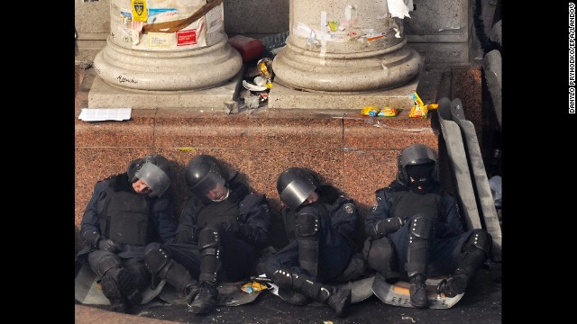Riot police officers rest against a column in Independence Square on February 19.