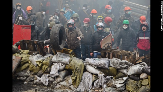 Protesters stand behind a barricade in Kiev on February 20.