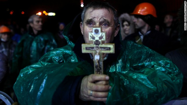 A protester holds a crucifix as he prays in Independence Square early February 20.
