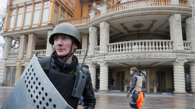 A protester guards the entrance to Ukrainian President Viktor Yanukovych's abandoned countryside residence outside of Kiev on Saturday, February 22. Ukrainian security and volunteers from among the Independence Square protesters have joined forces to protect the presidential countryside retreat from vandalism and looting.