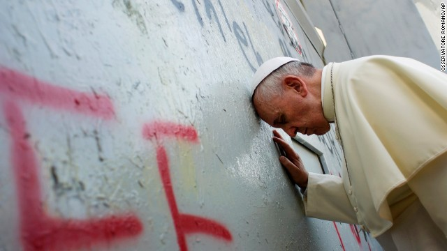 Pope Francis touches the wall that divides Israel from the West Bank, on his way to celebrate a mass in Manger Square next to the Church of the Nativity in Bethlehem
