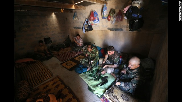 Peshmerga fighters clean their weapons at a base in Tuz Khormato on June 25.