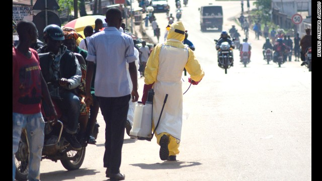A health worker with disinfectant spray walks down a street outside the government hospital in Kenema on Thursday, July 10.