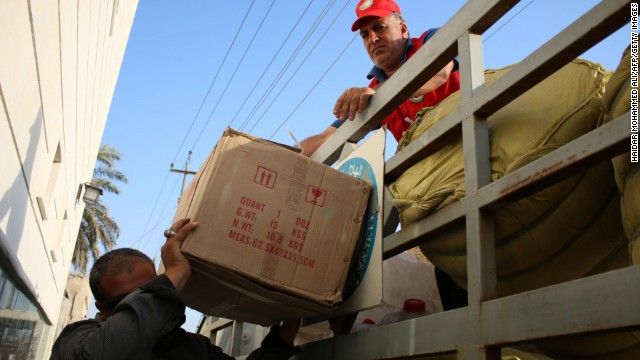 Volunteers of the Iraqi Red Crescent Society unload boxes of goods before distributing them August 14 to families who fled from ISIS.
