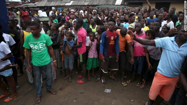 "A crowd enters the grounds of an Ebola isolation center in the West Point slum on August 16. The mob was reportedly shouting, ""No Ebola in West Point."""