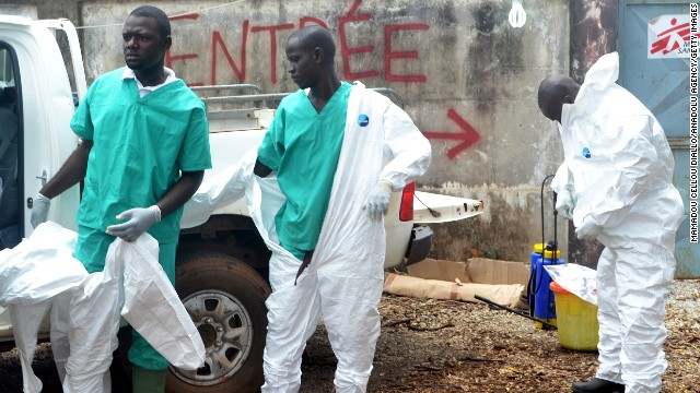 Members of a volunteer medical team wear protective gear before the burying of an Ebola victim Saturday, September 13, in Conakry, Guinea.