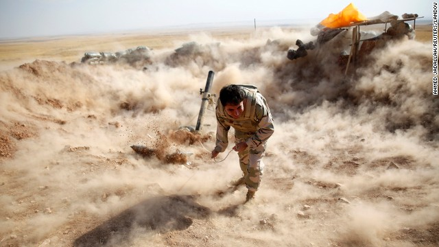 A Kurdish Peshmerga fighter launches mortar shells toward ISIS militants in Zummar on Monday, September 15.