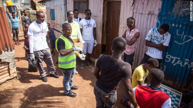A volunteer health worker in Freetown talks with residents on how to prevent Ebola infection and identify symptoms of the virus on September 20. Bars of soap were also distributed.