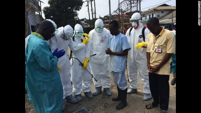 A team that handles the management of dead bodies prays with Saymon Kamara, far right, on September 22 in Monrovia. Kamara's mother died from complications of high blood pressure.