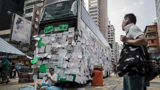 A pro-democracy demonstrator guards a bus covered with messages of support in Hong Kong on September 30.