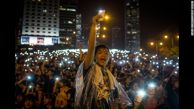 Protesters sing songs and wave their cell phones in the air after a massive thunderstorm passed over the Hong Kong Government Complex on September 30.