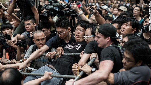 A pro-democracy protester holds on to a barrier as he and others defend a barricade from attacks by rival protest groups in the Mong Kok district of Hong Kong on Saturday, October 4.