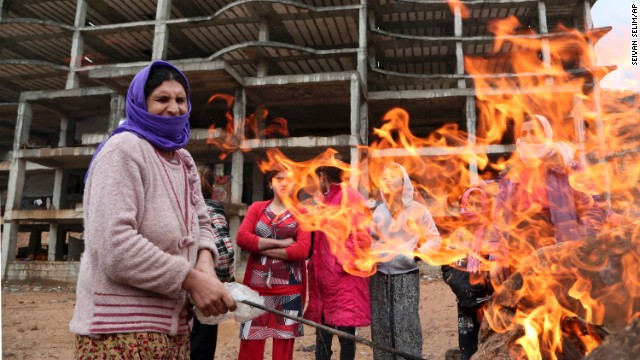A Yazidi woman displaced by ISIS militants tends to a fire Wednesday, December 10, at a shelter in Dohuk, Iraq.