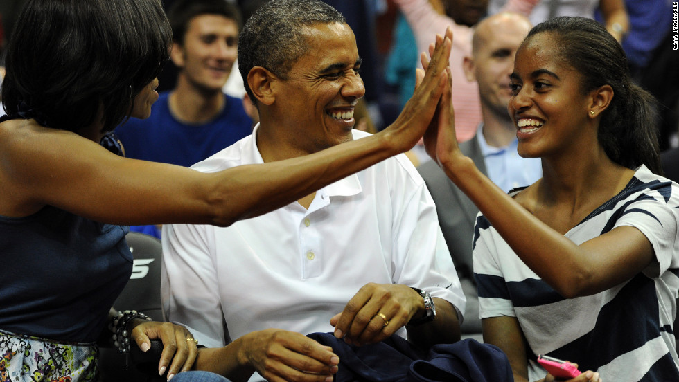 President Obama shares a laugh with his wife Michelle and daughter Malia, as the U.S. Senior Men's National Team plays Brazil in a pre-Olympic exhibition basketball game on July 16, 2012, in Washington.