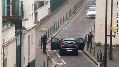 Armed gunmen face police officers near the offices of French satirical magazine Charlie Hebdo in Paris on Wednesday, January 7.