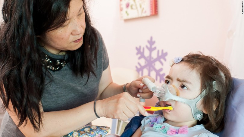 Julianna, who had Charcot-Marie-Tooth disease, once had nearly full use of her arms but eventually couldn't hold even a small toy without help. Here, her mother, Michelle Moon, brushes her teeth.
