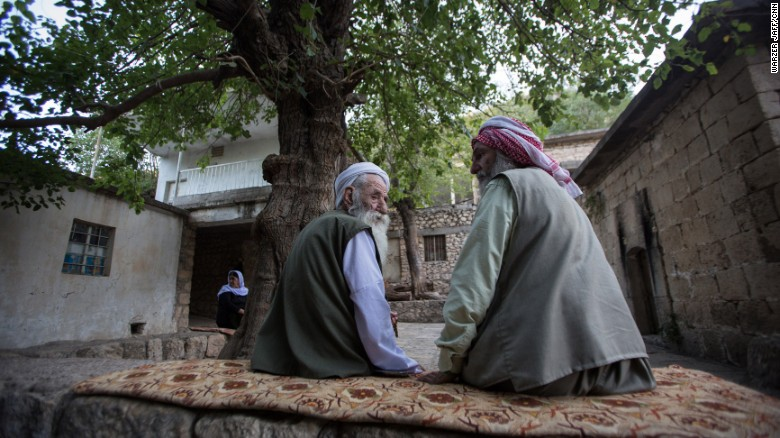 Two older Yazidi men talk under a tree.