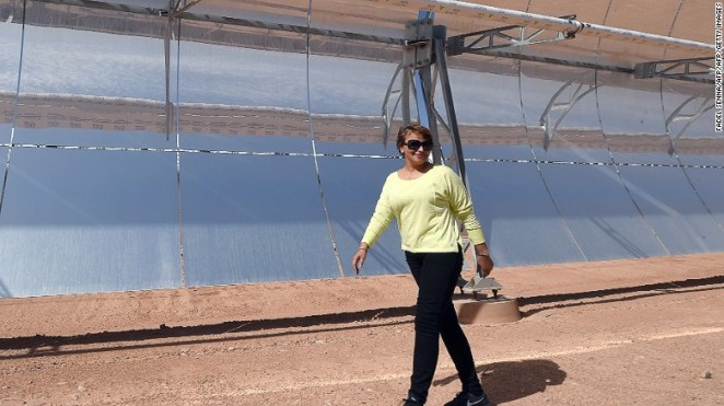 Morocco's environment minister Hakima El Haite walks in front of a solar array that is part of the Noor 1 solar power plant, which is due to start operating in a few weeks.