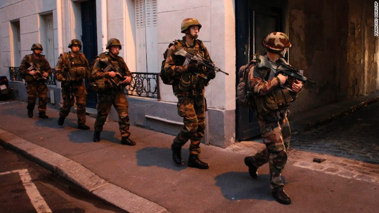 Soldiers operate in St. Denis, a northern suburb of Paris, Wednesday, Nov. 18, 2015. Authorities in the Paris suburb of St. Denis are telling residents to stay inside during a large police operation near France's national stadium that two officials say is linked to last week's deadly attacks. (AP Photo/Francois Mori)
