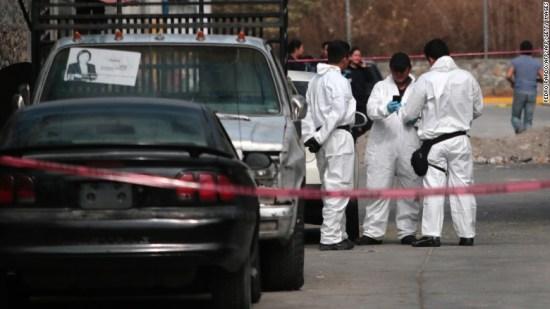 Forensic investigators gather outside residence of slain mayor.