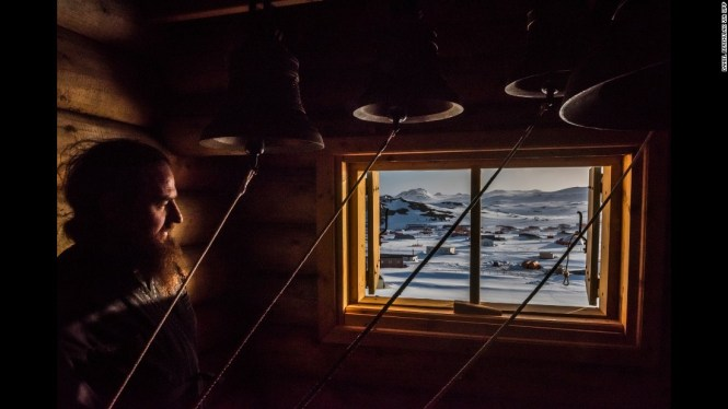 A priest looks out of a window after a vigil in Fildes Bay, Antarctica, on December 3. This story focuses on research teams from Chile, China and Russia who are seeking to explore commercial opportunities in Antarctica.