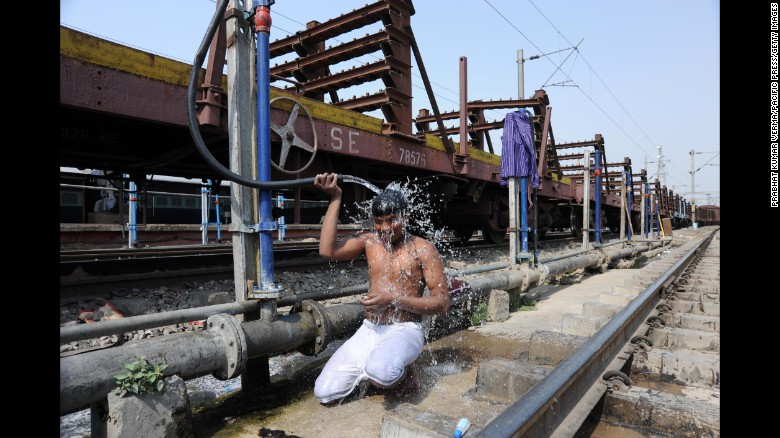 A commuter cools off at a railway junction during a hot day in Allahabad, India, on Saturday, May 14. Much of India is reeling from a heat wave and severe drought conditions that have decimated crops, killed livestock and left at least 330 million people without enough water for their daily needs.