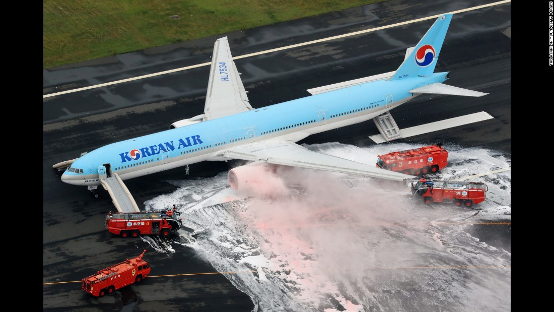 Firefighters in Tokyo spray foam on Korean Air Flight 2708 as smoke rises from an engine on Friday, May 27. The fire broke out before the airplane took off. All passengers and crew were safe.