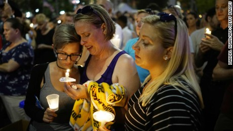 Women hold candles during a vigil for the victims of the Pulse nightclub shooting, on June 13, 2016 at the Dr. Phillips Center for the Performing Arts in Orlando, Florida.