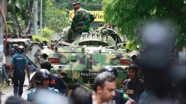 Bangladeshi soldiers and security personnel sit on top of armored vehicles as they cordon off an area near a restaurant popular with foreigners after heavily armed militants took dozens of hostages, in a diplomatic zone of the Bangladeshi capital Dhaka, Bangladesh, Saturday, July 2, 2016. Bangladesh forces stormed the Holey Artisan Bakery in Dhaka's Gulshan area Saturday morning, triggering explosions and finding bodies lying in pools of blood.