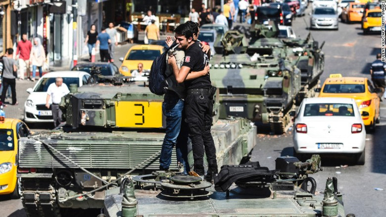 A Turkish police officer embracea a man on a tank after the military position was taken over at the Anatolian side at Uskudar in Istanbul on Saturday.