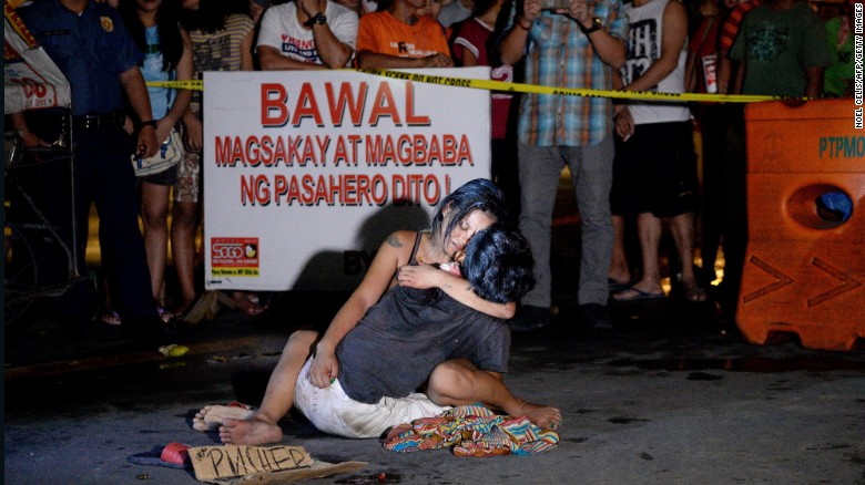 "A woman cradles her husband, next to a placard which reads ""I'm a pusher,"" who was shot dead in Manila on July 23, 2016."