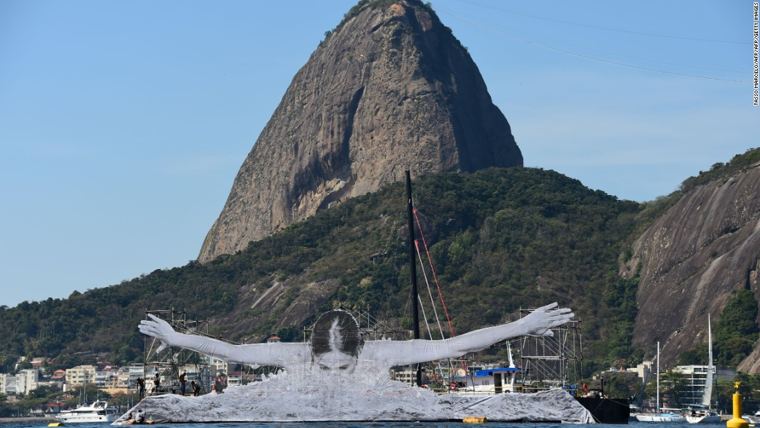 To date, JR has revealed four massive installations, each of which pay tribute to Olympic athletes: a swimmer in Guanabara Bay, a diver at Barra Beach, a crescent moon atop a residence for artists, and a high-jumper bending back over a building in the Flamengo neighborhood.