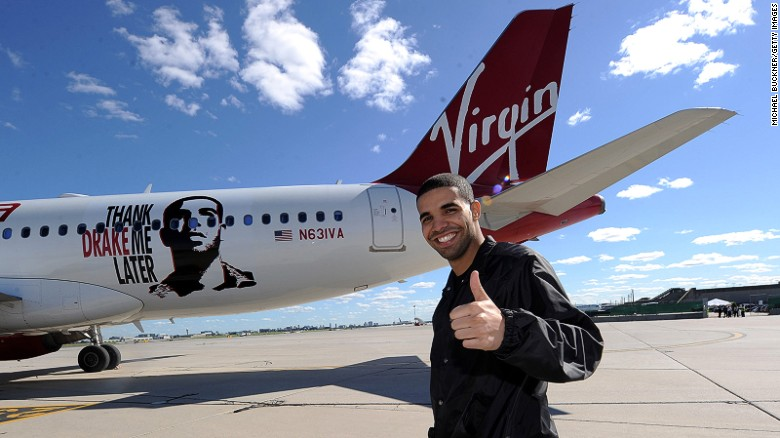 Virgin America has named several planes after celebrities. Pictured in 2010, Canadian R&B star Drake poses in front of Air Drake, which was named to celebrate Virgin America's first international flight to Toronto. <br />