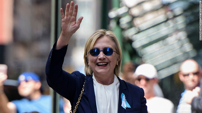 US Democratic presidential nominee Hillary Clinton waves to the press as she leaves her daughter's apartment building after resting on September 11, in New York.