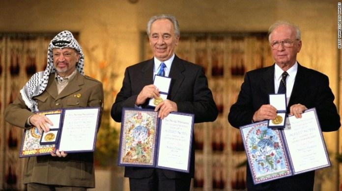 Palestinian leader Yasser Arafat (L), Israeli Foreign Minister Shimon Peres (C) and Israeli Premier Yitzhak Rabin display their Nobel Peace Prizes.