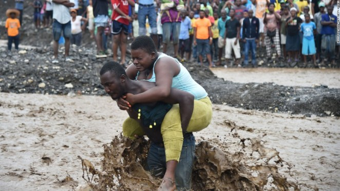A man carries a woman across a river at Petit Goave where a bridge collapsed during the rains of the Hurricane Matthew.
