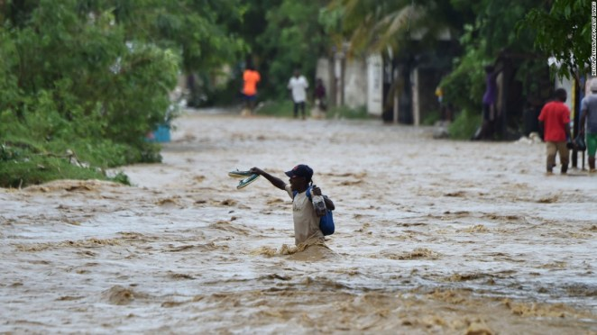 People try to cross the overflowing La Rouyonne river in the commune of Leogane.