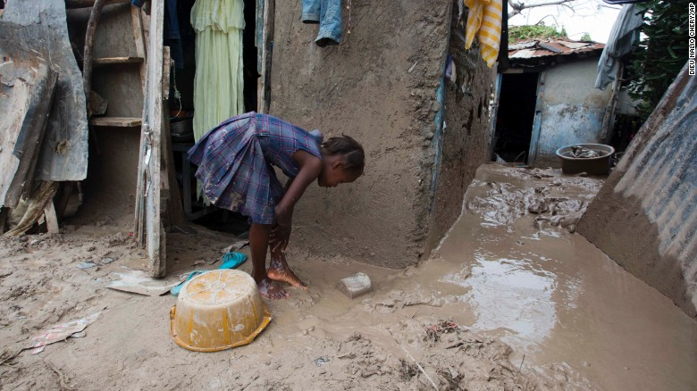 """A girl washes mud from her feet after Hurricane Matthew passed through Les Cayes, Haiti, on Thursday, October 6. <a href=""""http://www.cnn.com/2016/10/04/americas/hurricane-matthew/index.html"""" target=""""_blank"""">The damage from Hurricane Matthew</a> was especially brutal in southern Haiti, where sustained winds of 130 mph punished the country."""