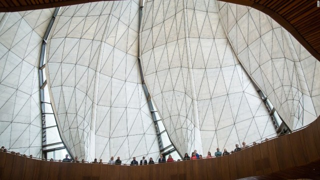 Nine wing-like panels of translucent cast glass form the temple dome, converging 90 feet above the ground.