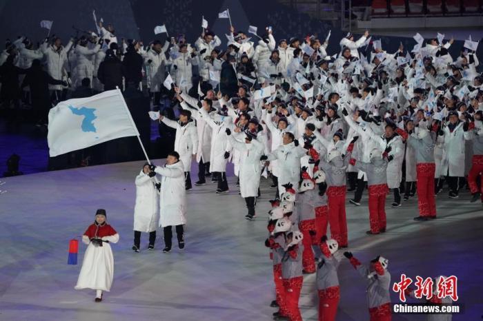 数据图:当地时间2018年2月9日晚,第23届冬季奥运会开幕式在韩国平昌举行。 图为朝鲜代表团和朝鲜代表团手拉手进入会场,中国新闻社记者崔楠摄。