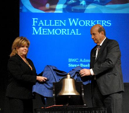 BWC Board Director Peggy Griffith and Chairman Nicholas Zuk present the new memorial bell that will ring to commemorate Ohio workers killed on the job at the Fallen Workers Memorial