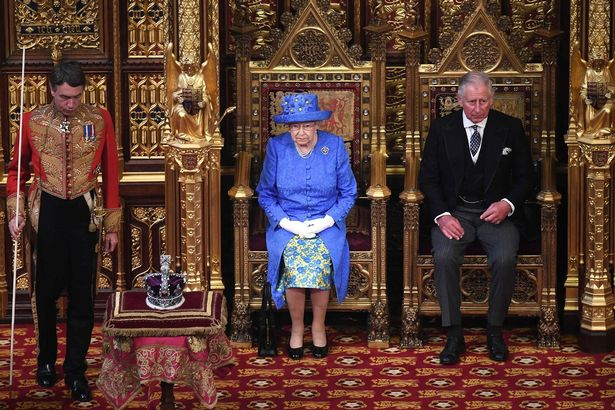 The Queen and Prince Charles on thrones in the House of Lords for the State Opening of Parliament, with the Imperial State Crown on a stand