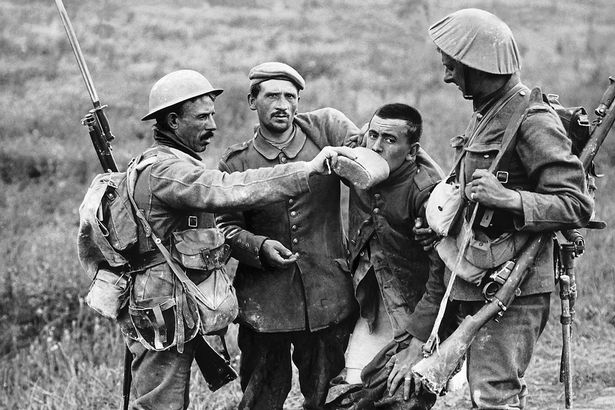 A British soldier giving a wounded German prisoner some water to drink, near La Boisselle, during the Battle of the Somme, 3 July 1916. Photographed by the Daily Mirror's photographer Ernest Brooks.